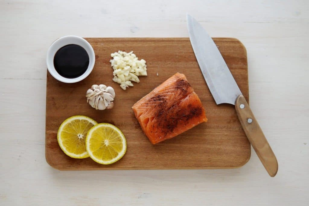 Salmon, lemon, garlic cloves, garlic chopped up, knife on cutting board, soy sauce, lazy girl health tips