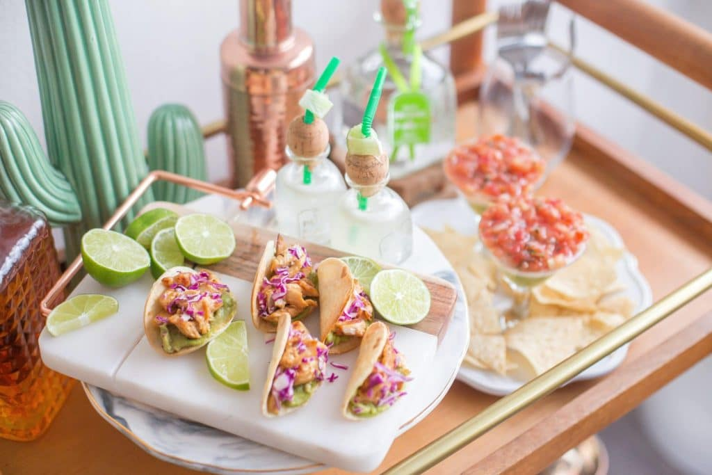 Tacos, salsa, patron, margaritas, lunch wrap, chips presented on serving cart with cheese cutting board