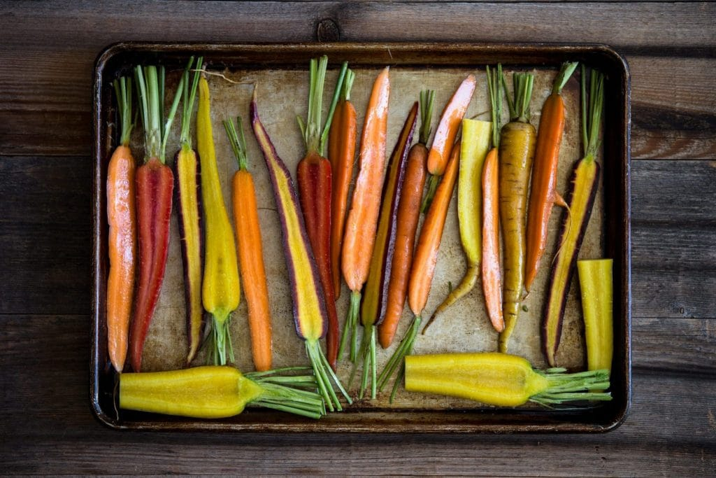 Orange carrots, yellow carrots, red carrots with olive oil on a roasting pan