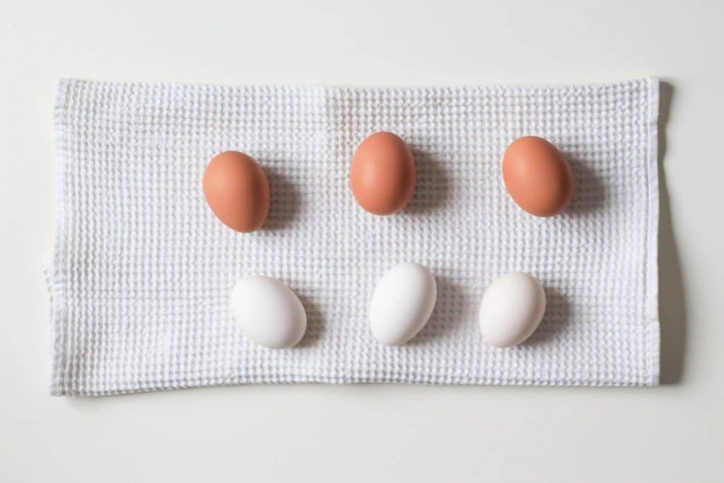 Three brown eggs and three white eggs on a white kitchen waffle towel on white background