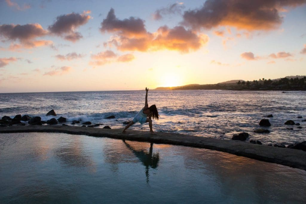 A woman doing yoga at sunset in a white dress on the side of a pool out of a funk