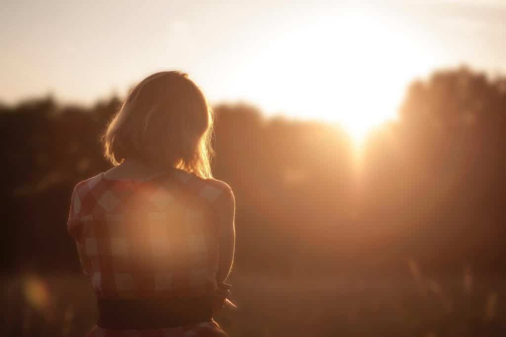 blonde woman with checkered red shirt staring at sunrise, out of a funk