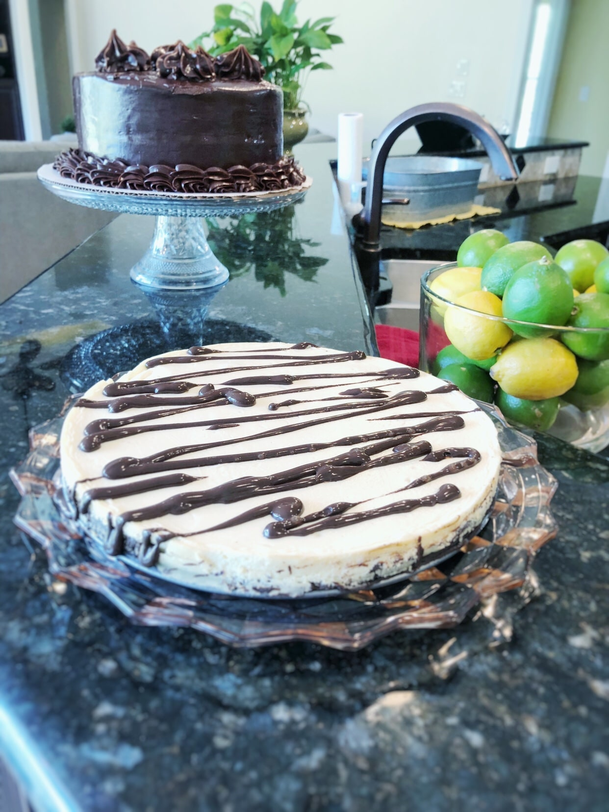 Keto Brownie Cheesecake, low carb, yellow lemons, green limes, plastic plate on a black marble counter, birthday, whole chocolate cake, kitchen