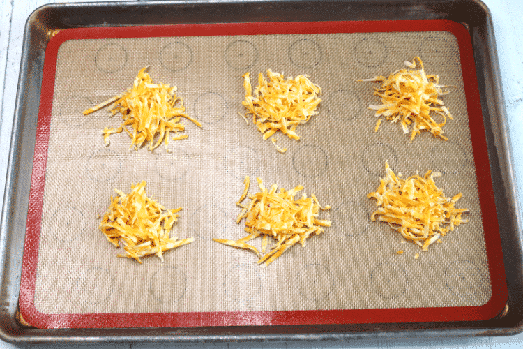 Shredded cheese mounds on silicone baking mat ready for the oven